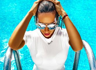 fashion photo of sexy hot beautiful girl model with dark hair in white swimwear coming out of swimming pool in sunglasses and touching her hair
