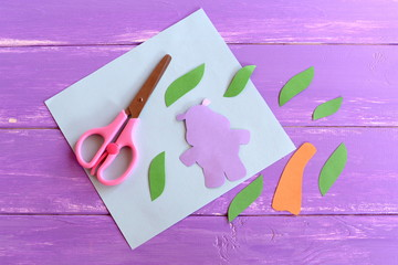 Hippopotamus, leaves, palm tree trunk cut from colorful paper. Set to make a Africa kids card. Stationery on wooden background. Children art project using a colored paper