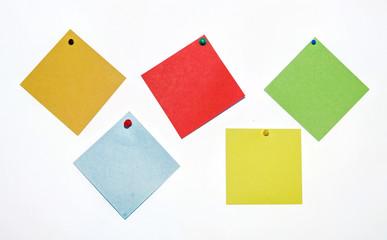 bunte Notizzettel mit Pin an weisser Wand