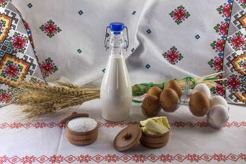 Milk bottle, eggs, salt, butter and ears of barley on the background in ethnic style