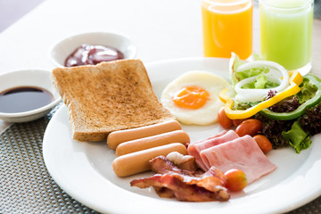 Breakfast set, bread, orange juice , guava juice, fried egg,ham,