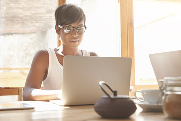 Young female freelancer working on laptop in cosy caf?. Good-looking dark-skinned woman with short hair and white top typing on computer in morning light. Productive job concept at comfy place.