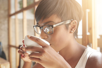 Sideways portrait of young female with chocolate skin. Focused business woman with pixie cut and diamond earrings drinking her morning coffee. Attractive girl in spectacles making plans for the day.