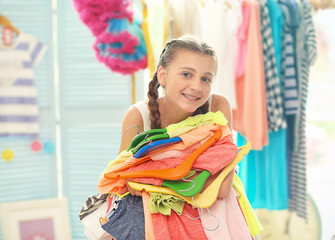 Pretty girl holding pile of clothes