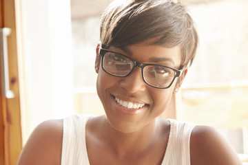 Nice close-up portrait of young girl in geeky glasses with pixie cut. Intelligent Spanish woman with shinny smile and brown eyes happily looking at camera. Successful lifestyle concept and happiness.