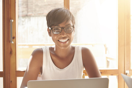 Smiling Spanish woman in white tank top and spectacles enjoying her studying. Smart beautiful female student sitting with laptop and exploring new topics for her education in morning light indoors.