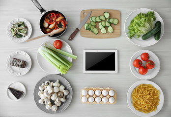Tablet with ingredients. Food blog concept, top view