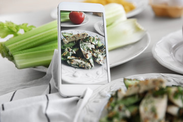 Tasty salad and cellphone. Food blog concept