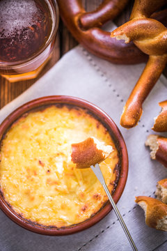 worming cheese fondue with pretzel at winter
