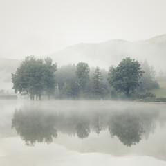 Mgła nad jeziorem o świcie z drzewami i górami odzwierciedlonymi w - 117073082