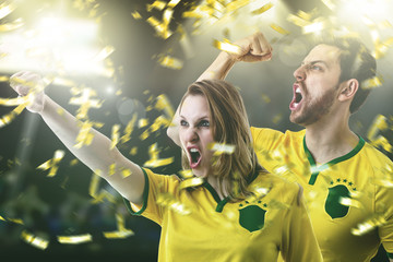 Couple fan celebrating in the stadium on yellow and green uniform