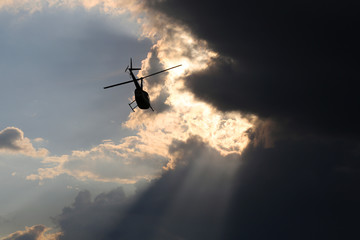 Helicopter silhouetted against darkening sky