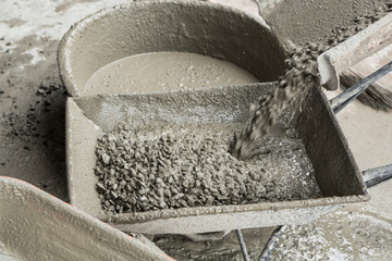 Motion Blur of Cement concrete pouring from cement truck into a cart mortar during for buildings construction.