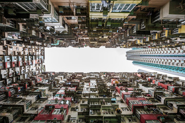 Hong Kong - May 31, 2015 :  Back of crowded buildings stand  surrounded the small common area, shooting in vertical view compares with modern building in  Hong Kong.