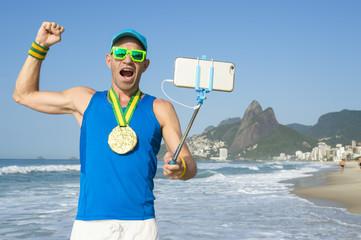 Athlete with gold medal posing for a celebratory selfie at Ipanema Beach, Rio de Janeiro, Brazil