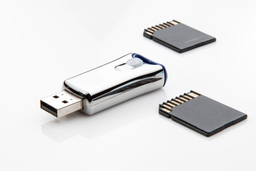 USB flash drive and two micro sd cards on white background