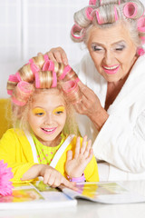 Senior woman and granddaughter doing hairstyle
