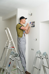 Electrician installing an electrical fuse box .