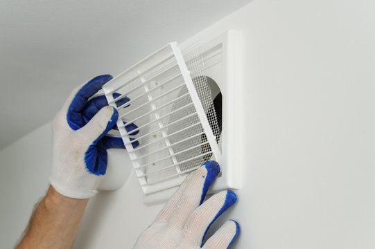 Worker installs ventilation grille.