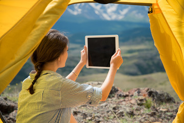 girl in the tent photographs mountains on the Tablet
