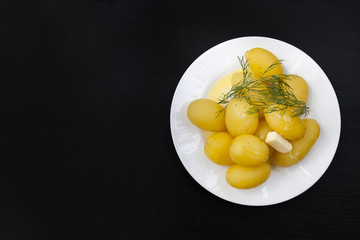 Boiled potatoes with dill and butter in white plate on black slate stone background, top view