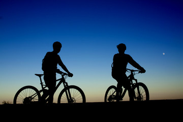 Two cyclists on the background of night sky and moon