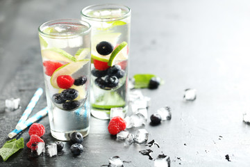 Detox water in glasses with berries on wooden table