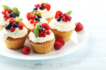 Tasty cupcakes with berries on white wooden table