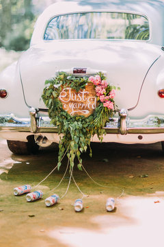 Vintage wedding car with just married sign and cans attached, close-up