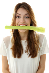 Beautiful girl eating celery, isolated on white