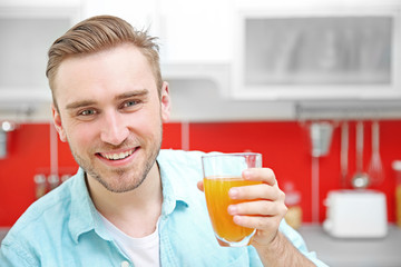 Handsome man with juice in kitchen