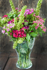 bouquet of garden Turkish carnations in a vase on a wooden backg