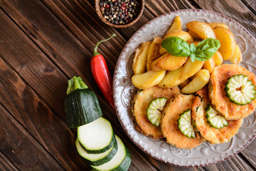 Breaded fried zucchini with American potatoes and cucumber