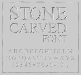 Stone Carved font. Alphabet on rock plate. Chips and scratches.