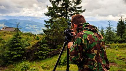 Photographer taking photo of mountain landscape, Carpathian, Ukraine
