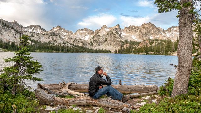 Man in the think position at a mountain lake