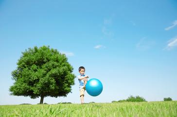 広場でボールで遊ぶ男の子