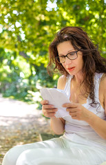 mature woman with glasses reads paper