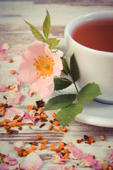Vintage photo, Cup of tea with wild rose flower on old rustic wooden background