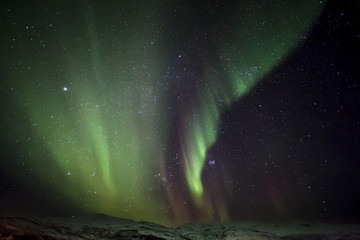 Strong bright green aurora northern lights over mountain