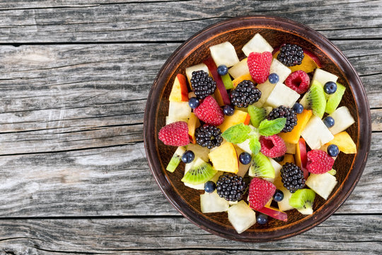 delicious fruit  and berry summer salad decorated with mint