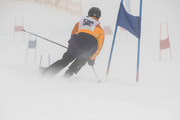 Slalom racer on a low visibility day wearing black, orange and yellow