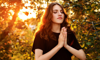The girl prays in nature eyes closed.