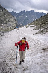 Young female hiker crossing snow field near Rysy peak in High Tatras National Park, Slovakia.