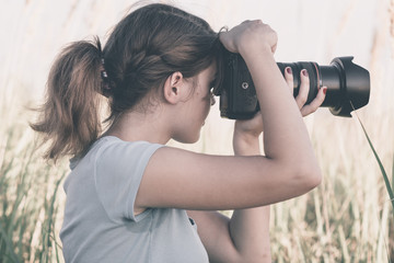 Vintage portrait of a beautiful young woman who likes to take pictures of nature