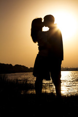 young couple express their feelings in a kiss at dawn on nature