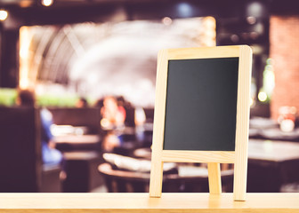 Blackboard with easel (menu board) on wooden table with blur bok
