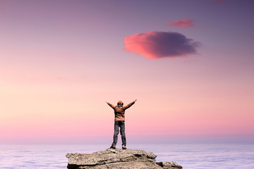 Man standing on the top of the mountain over clouds