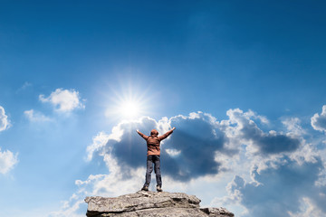 Man standing on the top of the mountain over blue sunny sky
