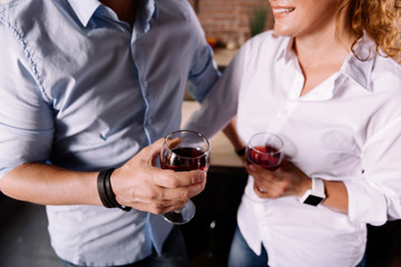 Hands of couple with wine glasses